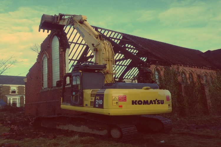 A Komatsu JCB demolishing the old St. Mary's church in Skewen, Swansea.